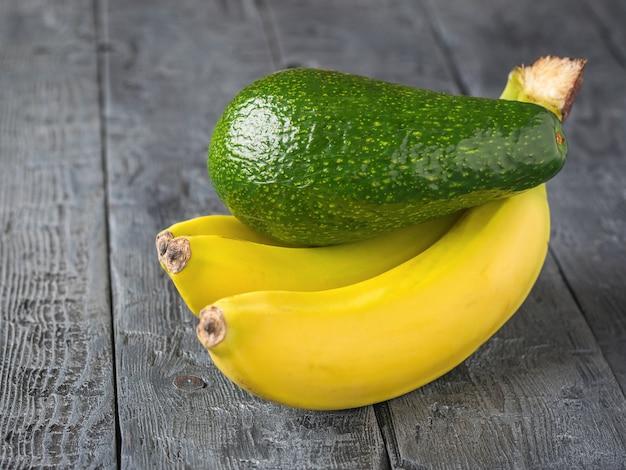 Rijpe sappige vruchten van banaan en avocado op rustieke houten tafel.
