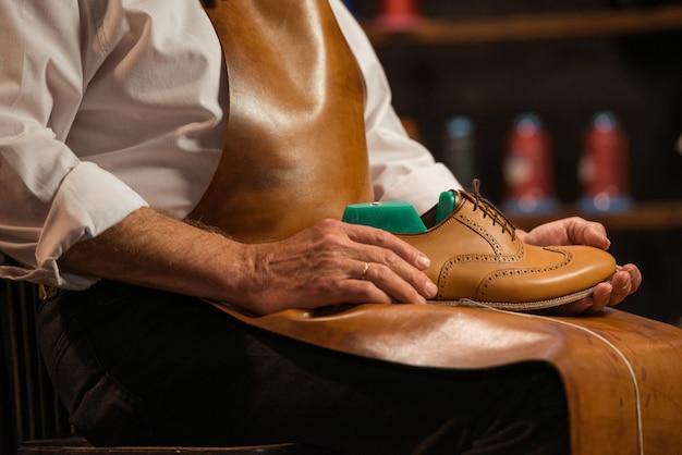 Rijpe schoenmaker die in workshop schoenen maakt