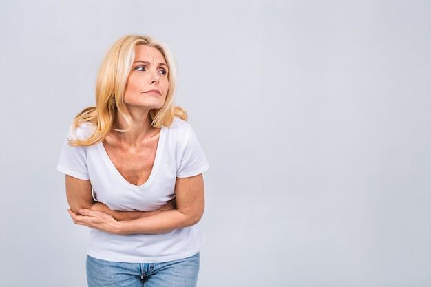 Rijpe senior blonde vrouw in casual met buikpijn geïsoleerd op een grijs witte achtergrond. sterke pijn in de maag.