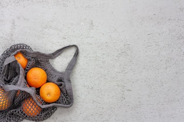 Rijpe sinaasappels in grijs eco katoenen koordzakje