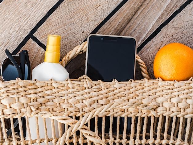Rijpe sinaasappels, rieten mand, zonnebrandcrème en zonnebril. bovenaanzicht, close-up. concept van vrije tijd en reizen
