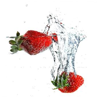 Rijpe smakelijke aardbeien vallen in helder water