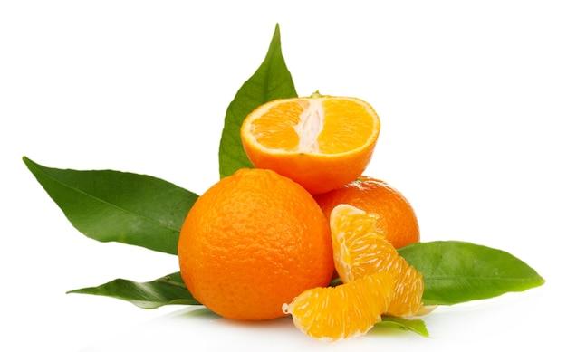 Rijpe smakelijke mandarijnen met bladeren en segmenten op wit