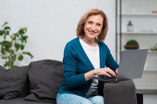 Rijpe smileyvrouw die laptop met behulp van
