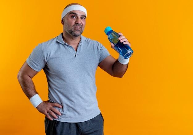 Rijpe sportieve man die in de fles water van de hoofdbandholding naar de voorzijde met ernstig gezicht kijkt dat zich over oranje muur bevindt
