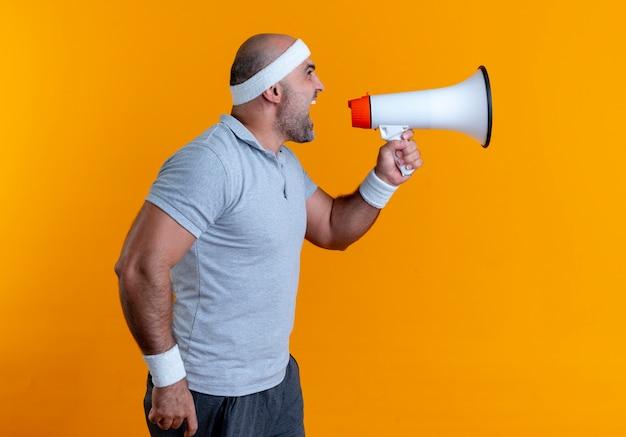 Rijpe sportieve man die in hoofdband aan megafoon schreeuwt die zich over oranje muur bevindt