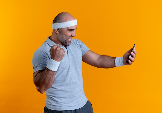 Rijpe sportieve man die in hoofdband het scherm van zijn mobiele telefoon bekijkt, blij en opgewonden balde vuist die zich over oranje muur bevindt