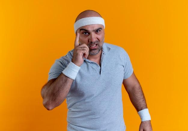 Rijpe sportieve man die in hoofdband naar voren kijkt die wijsvingerwaarschuwing met ernstig gezicht toont dat zich over oranje muur bevindt