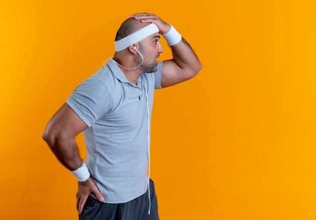 Rijpe sportieve man die in hoofdband opzij kijkt met verwarde uitdrukking die zich over oranje muur bevindt