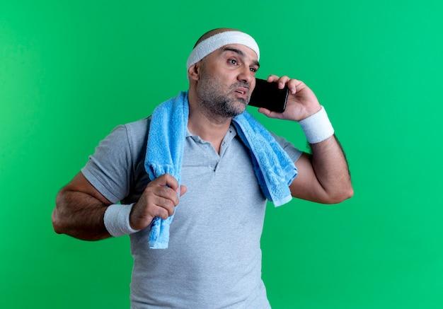 Rijpe sportieve man in hoofdband met handdoek om zijn nek op zoek verward tijdens het praten op mobiele telefoon staande over groene muur