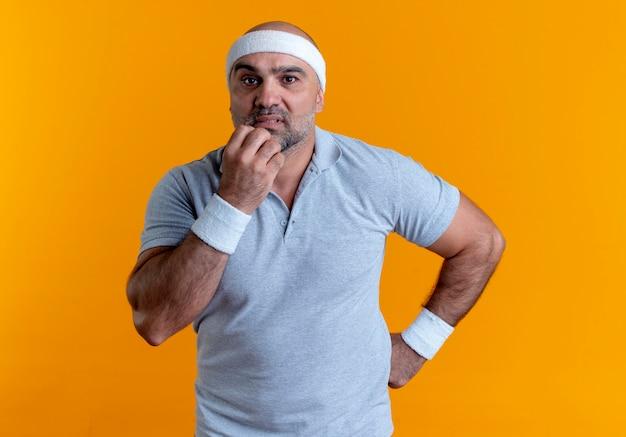 Rijpe sportieve man in hoofdband op zoek naar de voorkant beklemtoonde en nerveuze bijtende nagels staande over oranje muur