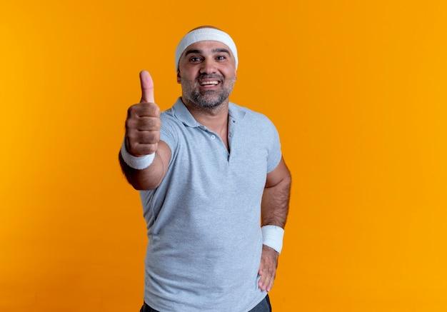 Rijpe sportieve man in hoofdband op zoek naar de voorkant lachend met blij gezicht met duimen omhoog staande over oranje muur