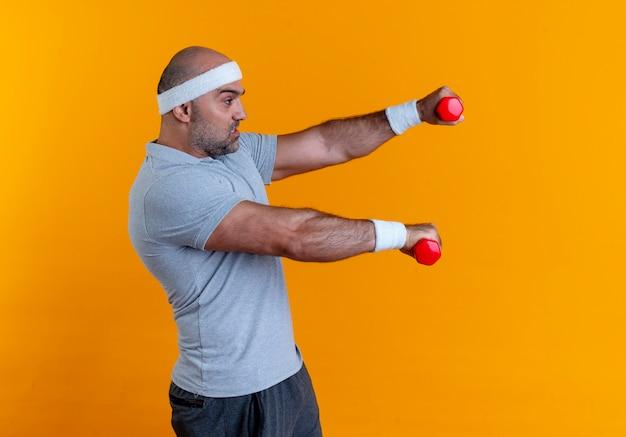 Rijpe sportieve man in hoofdband traint met halters op zoek gespannen en zelfverzekerd staande over oranje muur 10