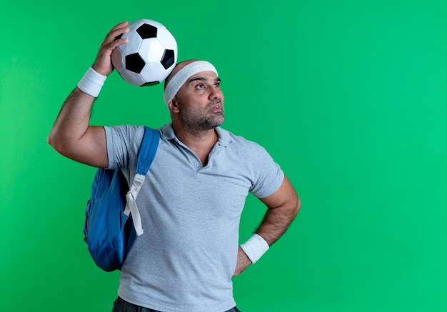 Rijpe sportieve mens in het voetbal die van de hoofdbandholding opzij verbaasd status over groene muur kijken Gratis Foto