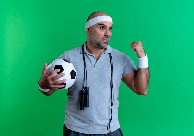 Rijpe sportieve mens in het voetbal die van de hoofdbandholding vuist opheft die opzij met ernstig gezicht kijken die zich over groene muur bevinden