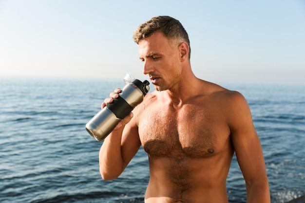 Rijpe sportman die zich met fles water bevindt die op het strand drinkt.