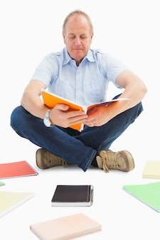 Rijpe student die van notitieboekje bestudeert