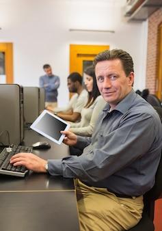 Rijpe student in pc van de de holdingstablet van de computerklasse
