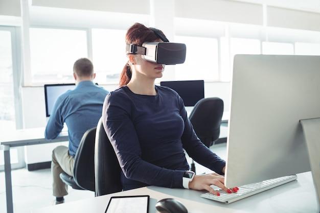 Rijpe student in virtuele werkelijkheidshoofdtelefoon die computer met behulp van