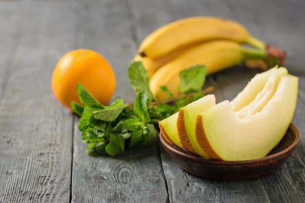 Rijpe stukjes meloen op klei kom, banaan, munt en oranje op houten tafel.