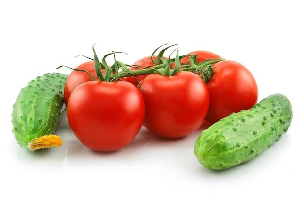 Rijpe tomaten en komkommers geïsoleerd op wit