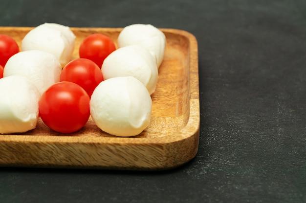 Rijpe tomaten en mozzarella ballen op houten plaat - italiaanse voedselingrediënten met kopie ruimte.