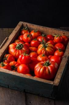 Rijpe tomaten in een houten kist verse groenten op een zwarte houten achtergrond