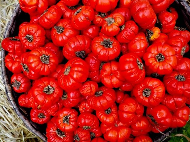 Rijpe tomaten in een mand op een aard. plat leggen