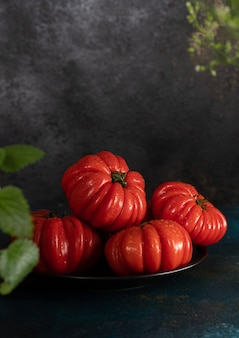 Rijpe tomaten liggen op een zwarte plaat. groenten voor het maken van sap. rode groente op een zwarte achtergrond, zijaanzicht.