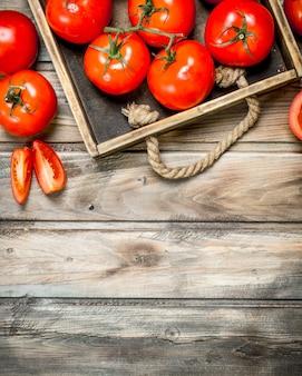 Rijpe tomaten op dienblad op houten tafel
