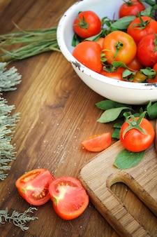 Rijpe tomaten op een oude houten tafel in rustieke stijl