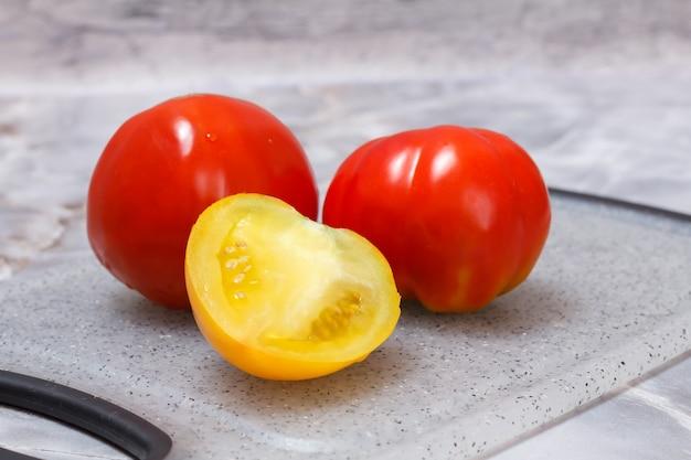 Rijpe tomaten op snijplank met grijze achtergrond.
