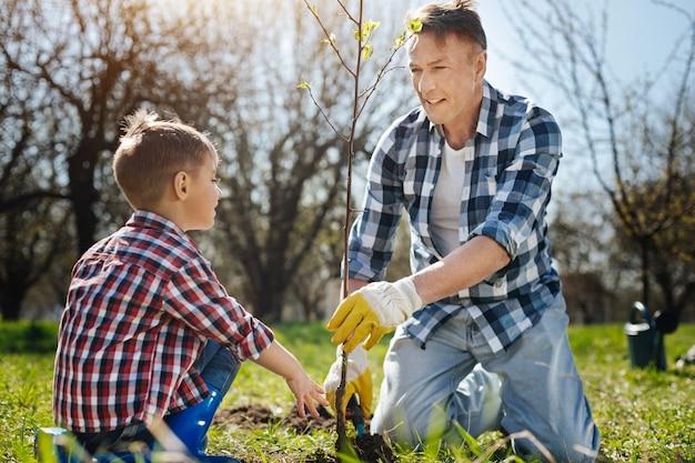 Rijpe vader die zoontje leert hoe hij voor de natuur moet zorgen door een boom in de tuin van een landhuis te zetten