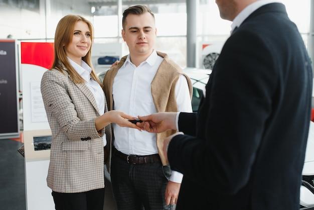 Rijpe verkoper die nieuwe auto toont aan een paar in toonzaal