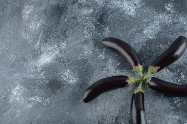 Rijpe verse aubergines op een grijze achtergrond.