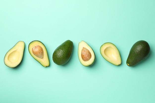 Rijpe verse avocado op mint achtergrond, bovenaanzicht