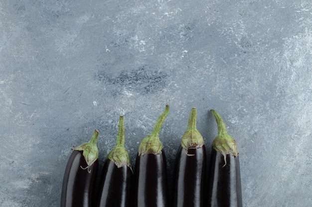 Rijpe verse paarse aubergines op een grijze achtergrond.