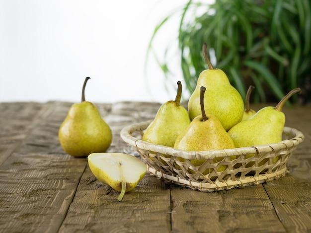 Rijpe verse peren in een mooie mand op de tafel.