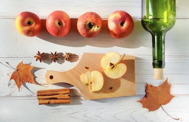 Rijpe verse, sappige rode appels, kruiden, fles en glazen met cider op een licht houten oppervlak.