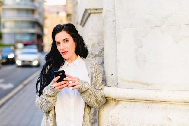 Rijpe verward en verloren vrouw die haar mobiele telefoon raadpleegt.