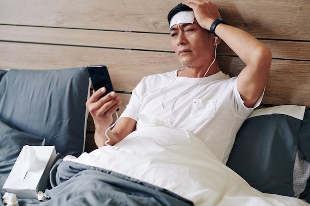 Rijpe vietnamse man die lijdt aan koorts en ernstige hoofdpijn die in bed ligt en zijn dokter belt