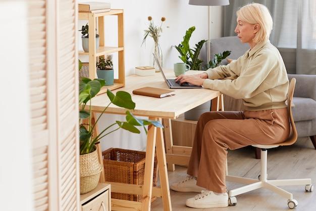 Rijpe vrouw aan de tafel zitten en typen op laptop die ze thuis online werkt