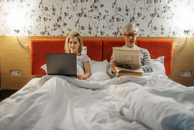 Rijpe vrouw bij laptop en echtgenoot met krant