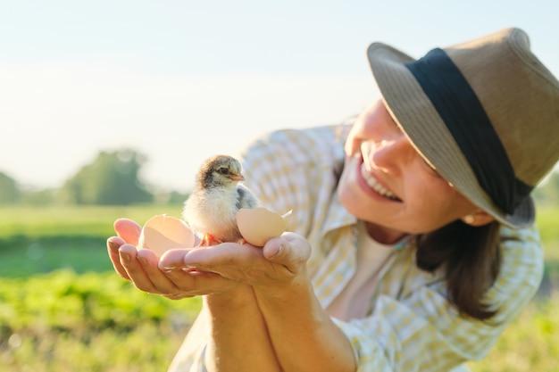 Rijpe vrouw boer met pasgeboren kuiken in haar hand