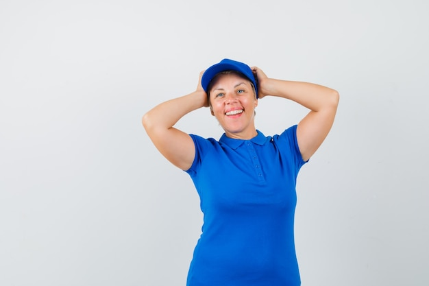 Rijpe vrouw clasping hoofd binnen dient blauw t-shirt in en kijkt blij.