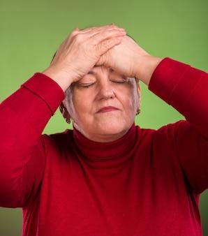 Rijpe vrouw die aan hoofdpijn op een groene achtergrond lijdt