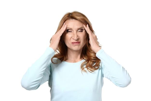 Rijpe vrouw die aan hoofdpijn op wit lijdt