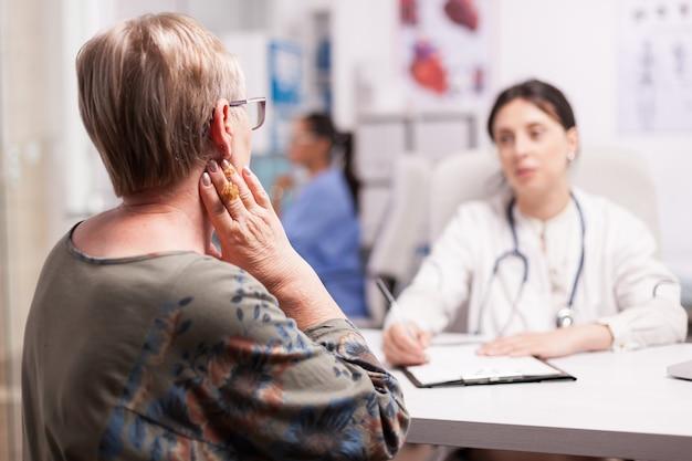 Rijpe vrouw die aan nekpijn lijdt tijdens overleg met arts in ziekenhuiskabinet. senior patiënt onderzoek.