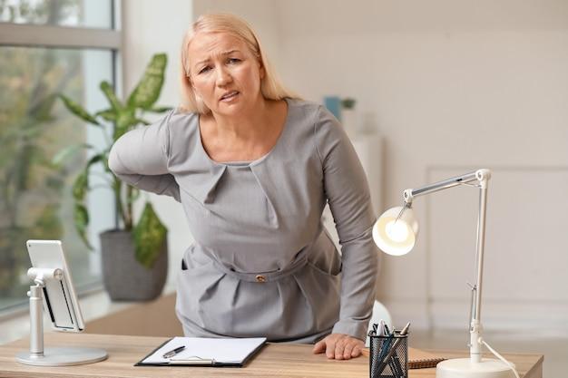 Rijpe vrouw die aan rugpijn in bureau lijdt