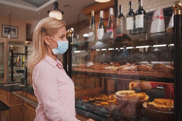 Rijpe vrouw die bij de bakkerij winkelt